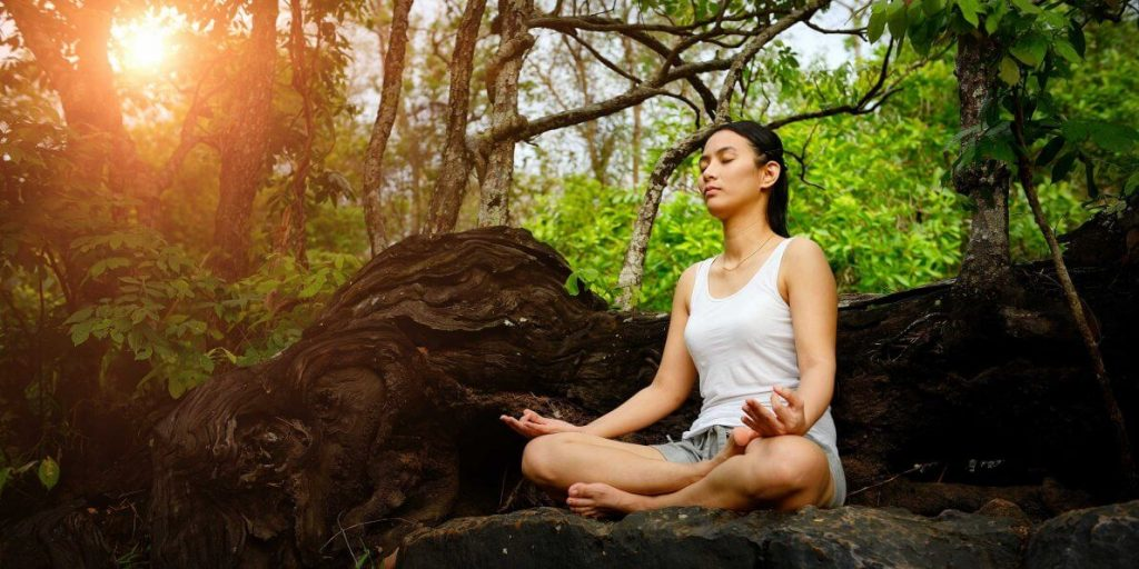 Woman meditating in the woods