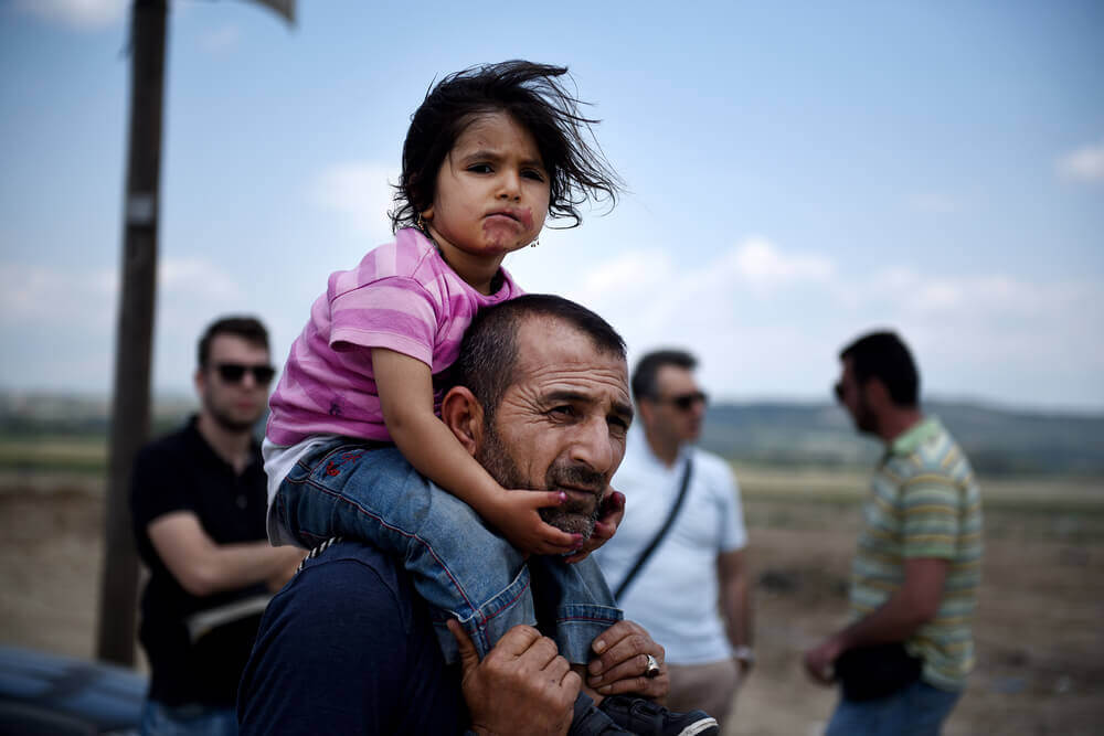 A Syrian man carries his daughter