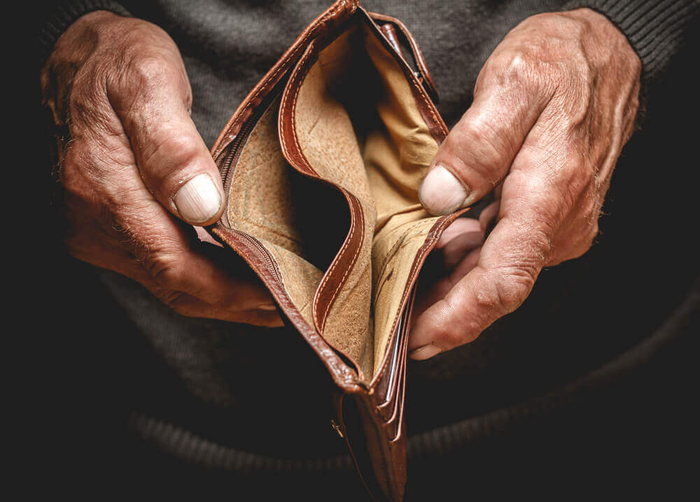 Empty wallet in the hands of an elderly man