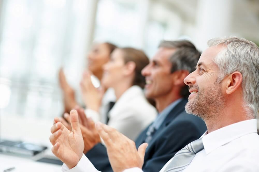 Group of happy business people clapping