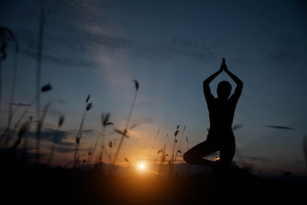 Silhouette of a young woman practicing yoga