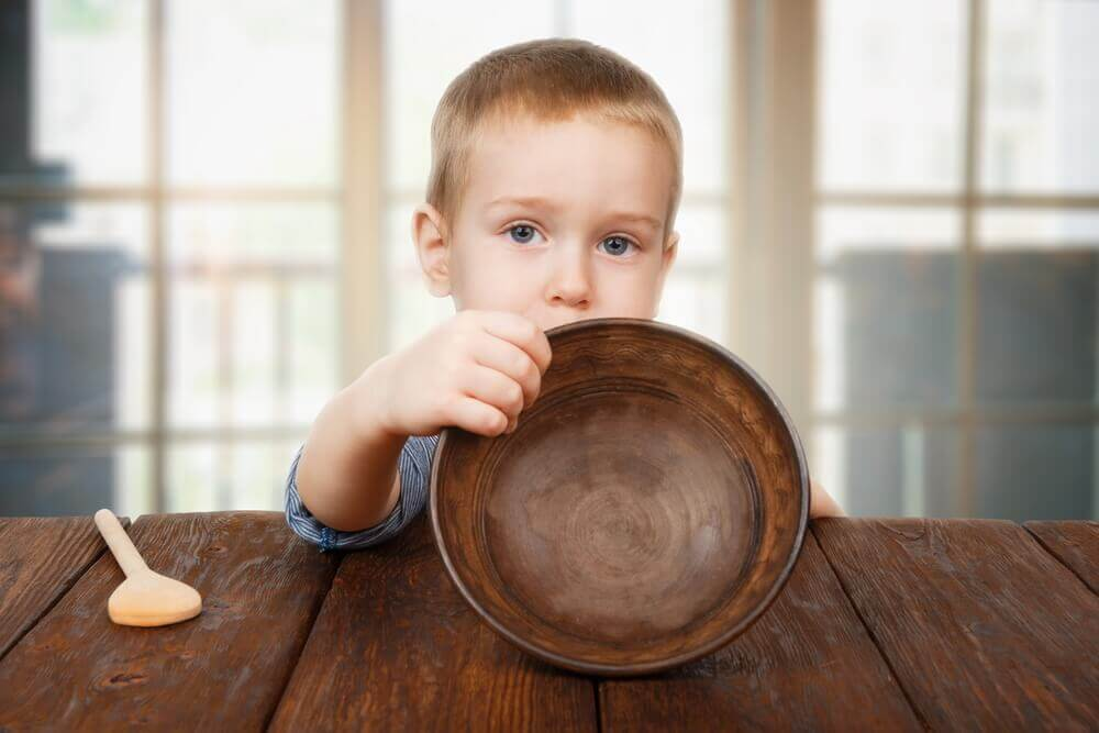 Small toddler boy shows empty bowl