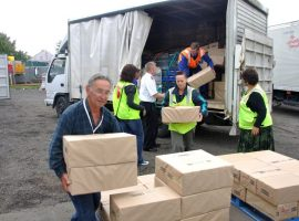 Volunteers unload food for victims