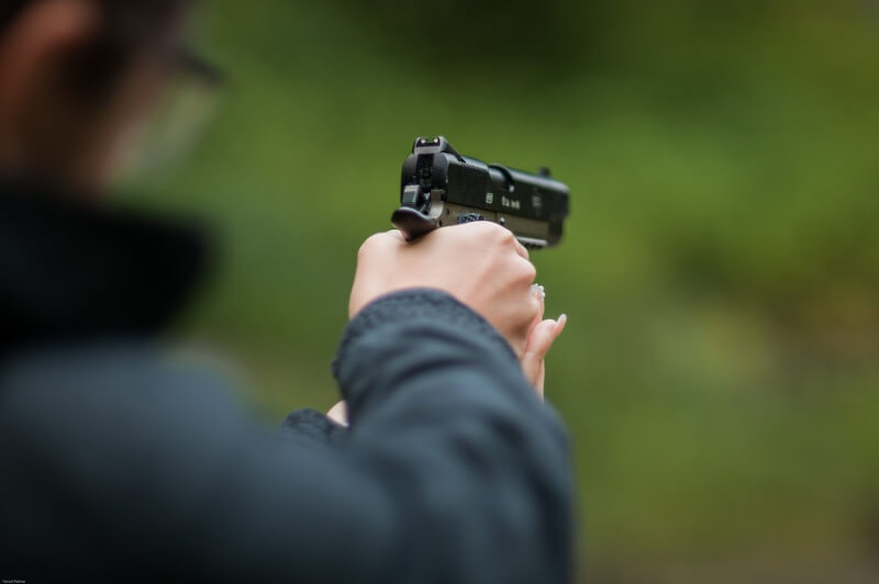 Detail of the hand of a woman holding a BB gun and targeting