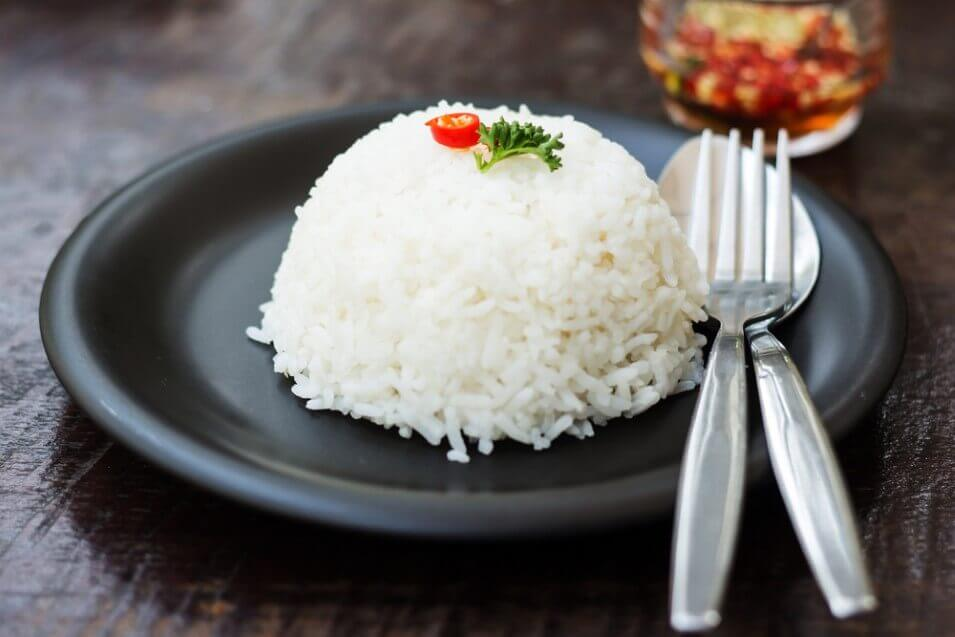 cooked rice with a spoon and fork on dish