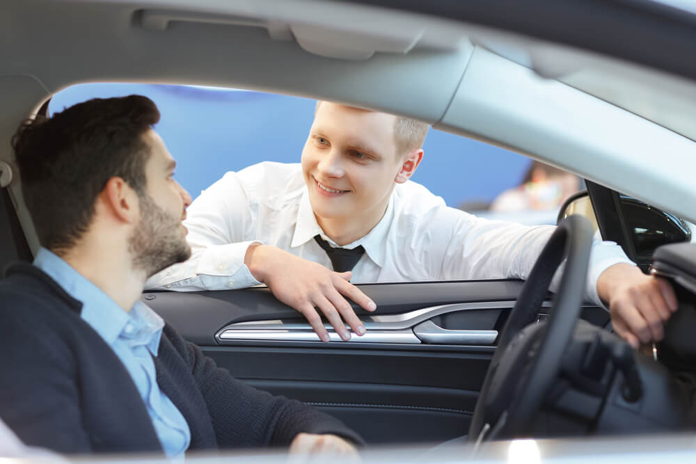 male client smiling to professional car dealer
