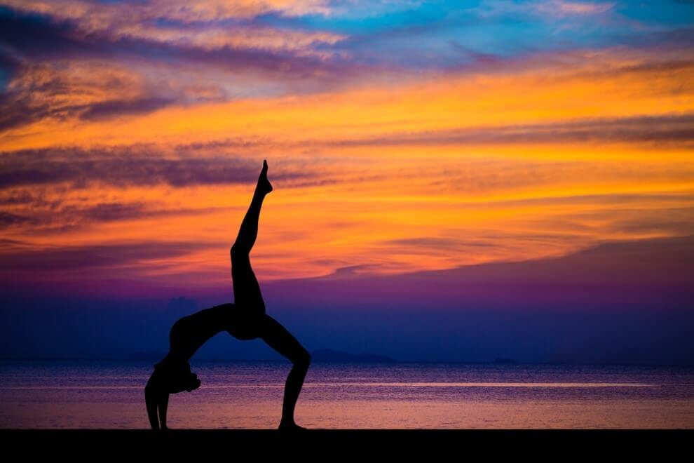 stunning sea and sunset is making yoga exercises
